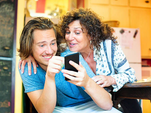 amused male teenager shows mobile phone game to delighted mother - mom spying stock photos and pictures