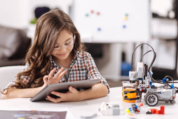 Amused teen girl using tablet in the science studio stock photo