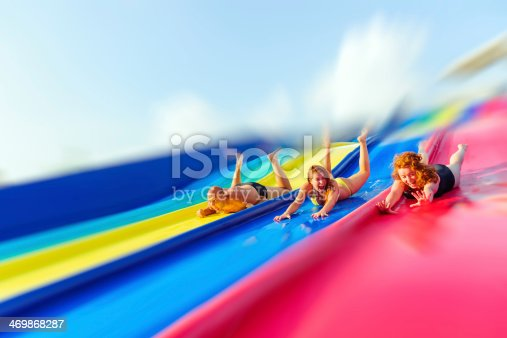 funny friends in water park laughing on water slide.
