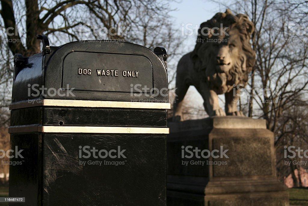 Amusing image of lion statue looking at dog waste bin royalty-free stock photo