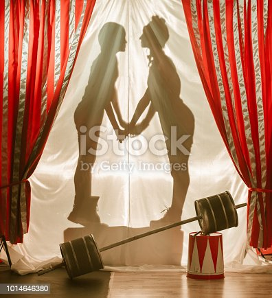 Silhouettes of kids (boy and girl) circus performers are on white translucent curtain. Children stand face to face and hold hands. Studio shooting on the striped theatrical curtain background