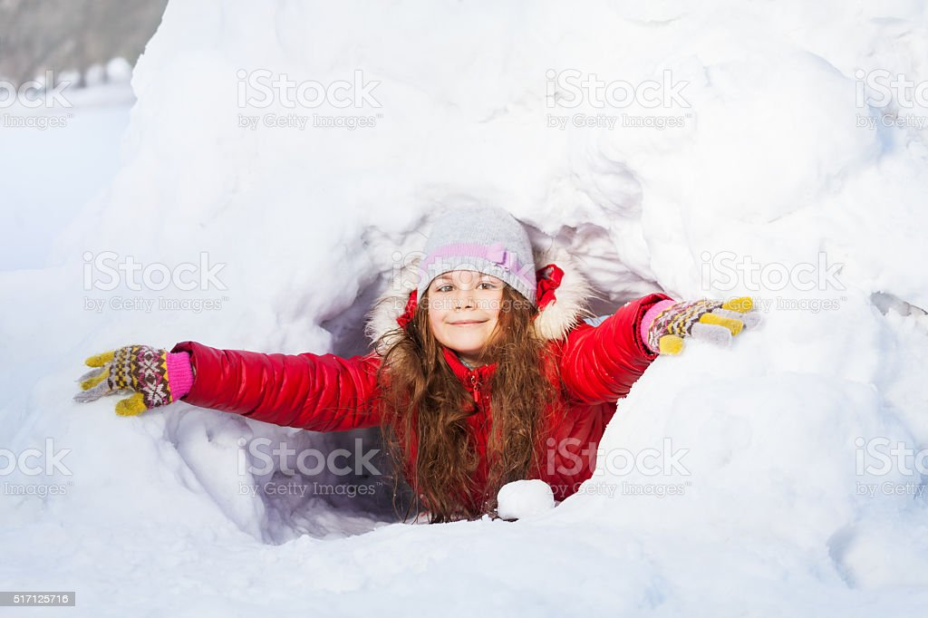 Amusing smiling girl in the winter at a snow cave stock photo