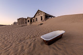 A photograph outside with an abandoned house on the horizon and a white bathtub lying in the rippled desert sand in the foreground, taken in the ghost town of Kolmanskop, Namibia.