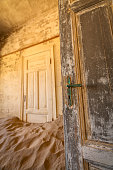 A close up vertical photograph of two old worn doors, with desert sand filling the abandoned room, taken in the ghost town of Kolmanskop, Namibia.
