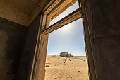 A close up photograph through an old, broken window, with desert sand and an abandoned house in the background, taken in the ghost town of Kolmanskop, Namibia.