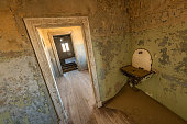 A photograph of an ancient washbasin and a door leading to an abandoned room, taken in the ghost town of Kolmanskop, Namibia.