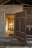 A vertical photograph inside an abandoned house, with an open door framing another room, taken in the ghost town of Kolmanskop, Namibia.