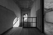 A black and white photograph inside an abandoned house at the top of a stairway, taken in the ghost town of Kolmanskop, Namibia.