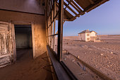 A photograph inside an abandoned house after sunset, with desert sand and a house visible through broken windows, taken in the ghost town of Kolmanskop, Namibia.