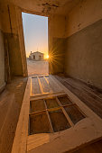 A dramatic vertical photograph inside an abandoned house at sunset, with an old door lying on the floor and a sunburst and house outside, taken in the ghost town of Kolmanskop, Namibia.