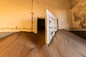 A photograph inside an abandoned house with an open white door submerged in the rippled desert sand, taken in the ghost town of Kolmanskop, Namibia.