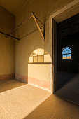 A vertical photograph inside an abandoned house with an open doorway leading into another room and a shaft of golden light streaming in the room, taken in the ghost town of Kolmanskop, Namibia.