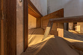 A photograph inside an abandoned house with an open door submerged in the rippled desert sand and golden sunlight streaming in, taken in the ghost town of Kolmanskop, Namibia.
