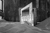 A black and white photograph inside an abandoned house with an open door submerged in the rippled desert sand, taken in the ghost town of Kolmanskop, Namibia.