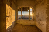A dramatic photograph inside an abandoned house at sunrise, with a golden sunburst and building through broken windows, taken in the ghost town of Kolmanskop, Namibia.