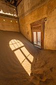 A vertical photograph inside an abandoned house with desert sand piled in the corner and golden sunlight streaming through a broken door, taken in the ghost town of Kolmanskop, Namibia.