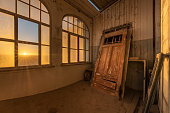 A dramatic photograph inside an abandoned house at sunrise, with a golden sunburst through broken windows and an ancient door buried in desert sand, taken in the ghost town of Kolmanskop, Namibia.