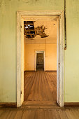 A vertical photograph inside an abandoned house with an open doorway leading into another room, taken in the ghost town of Kolmanskop, Namibia.