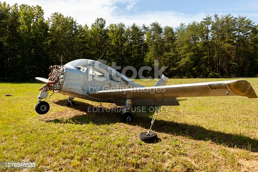 Indian Head, MD, USA 09/19/2020:  Close up isolated image of an abandoned rusty Beechcraft Musketeer A23 model single engine low wing light aircraft left on grassland in Maryland Airport.