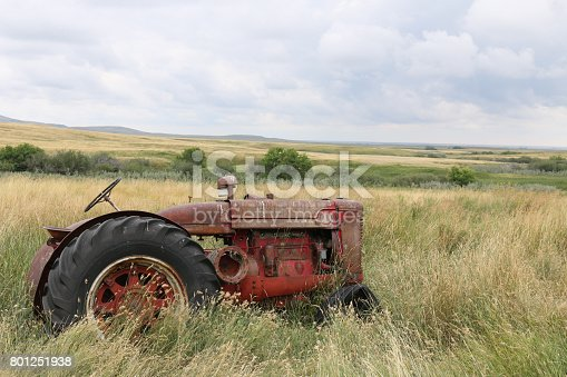 An old red tractor sits alone in a prairie field of tall grass.