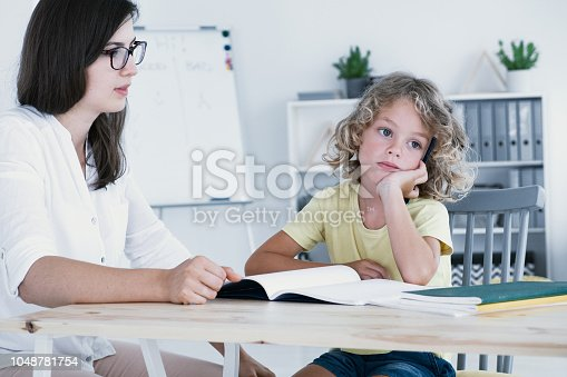 istock An absent-minded kid looking to the side and not at his homework notebook during a lesson with a tutor. 1048781754