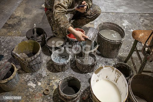 A man in stained clothes crouches next to a lot of dirty paint cans and pours water into them