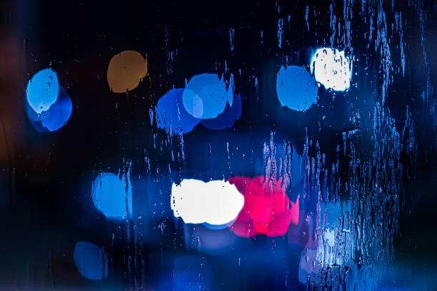 an abstract background of red and blue police lights bokeh trough wet glass at night close-up with selective focus stock photo