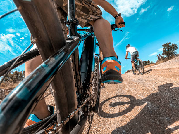 An action point of view of a cycler riding an e-bike in a race across the country side on a sunny day stock photo