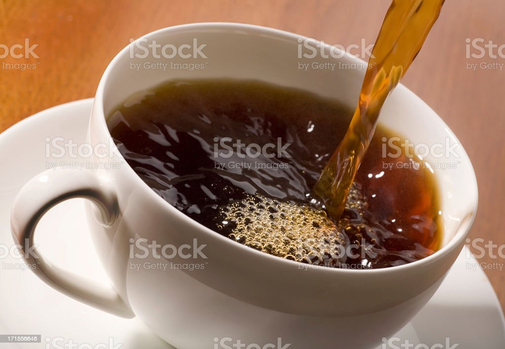 An action shot of black coffee being poured into a cup royalty-free stock photo
