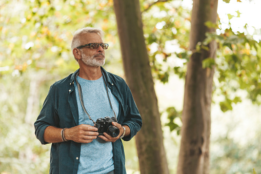 An active hobby of an elderly man with a beard outdoors. A pensioner takes pictures of nature with a camera while traveling.