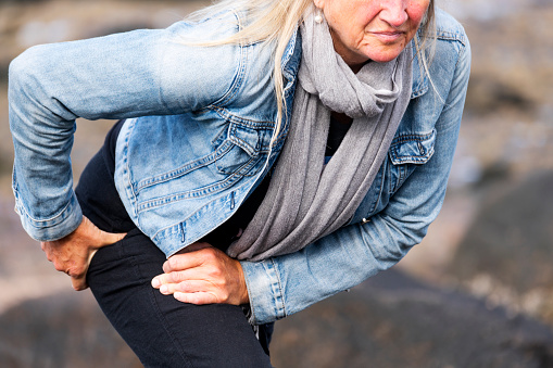 An active mature woman experiencing hip pain during a walk