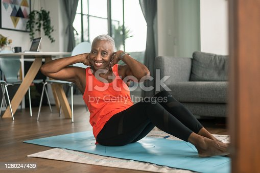 A senior black woman does sit ups from her lounge room on a blue yoga mat. She is wearing active wear and smiling at the camera.