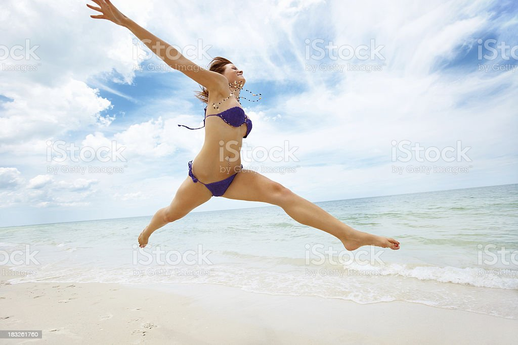 An active sexy female jumping on beach during summer vacation stock photo