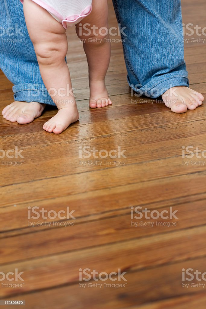 An adult assisting a child that is learning to walk royalty-free stock photo