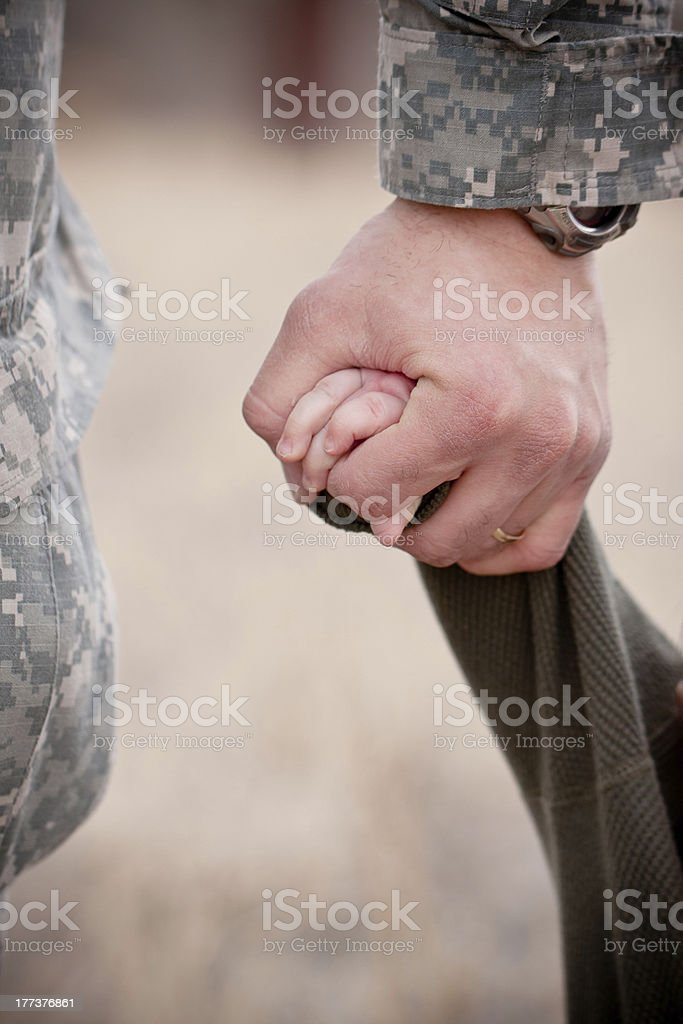 An adult hand in military fatigues holding a child's hand  stock photo