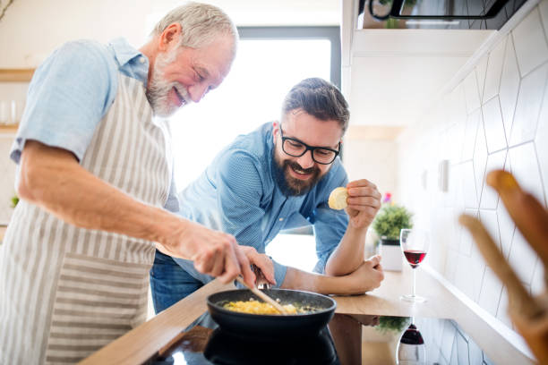 An adult hipster son and senior father indoors at home, cooking. stock photo