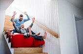 istock An adult hipster son and senior father indoors at home, having fun. 1182265947