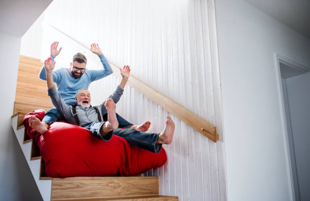 an adult hipster son and senior father indoors at home, having fun. - eccentrico foto e immagini stock