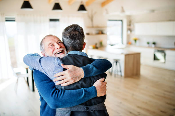An adult hipster son and senior father indoors at home, hugging. stock photo
