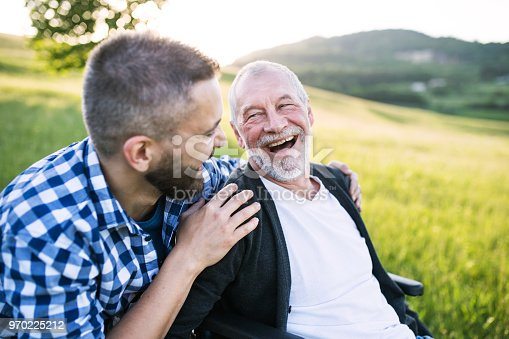 istock An adult hipster son with senior father in wheelchair on a walk in nature at sunset, laughing. 970225212