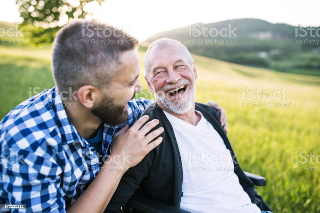 An adult hipster son with senior father in wheelchair on a walk in nature at sunset, laughing. stock photo