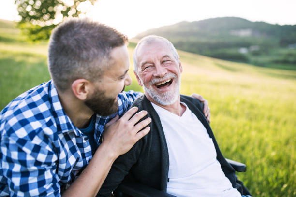 an adult hipster son with senior father in wheelchair on a walk in nature at sunset, laughing. - son stock photos and pictures