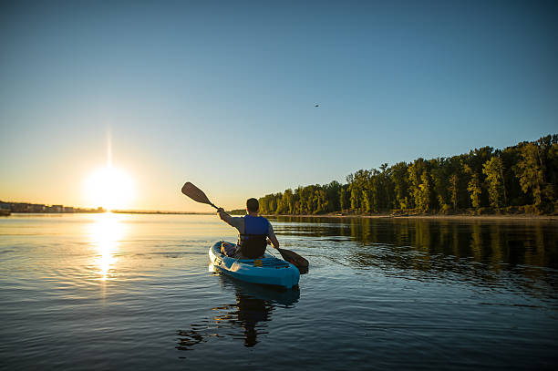an adult male is kayaking at sunset on a peaceful - caiaque - fotografias e filmes do acervo