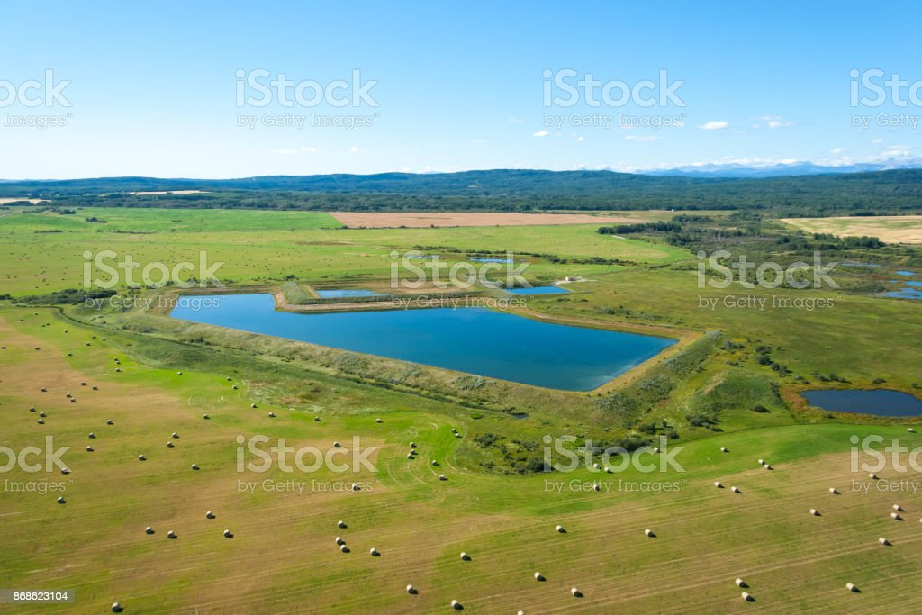 An aerial photo of farm land with hey barrels and small man made lake. stock photo