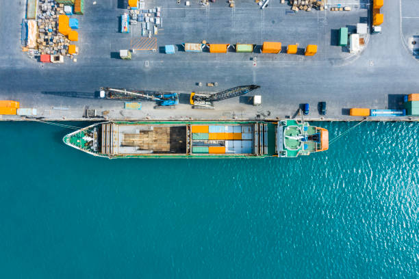 An aerial photograph of a container ship fixed at a commercial port. Lots of containers. Distribution. logistics. mooring stock pictures, royalty-free photos & images