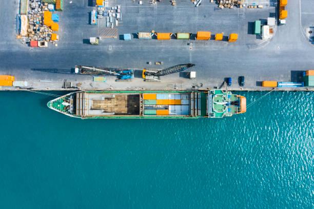een luchtfoto van een containerschip vast in een commerciële haven. - aangemeerd stockfoto's en -beelden