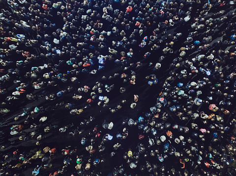 An aerial shot of the people gathered for an event. Crowded open-air meeting at the black background. A mass of people gathered to celebrate an event. Open-air night festival. City merrymaking.