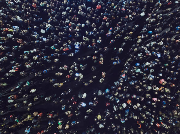 an aerial shot of the people gathered for an event. crowded open-air meeting at the black background. a mass of people gathered to celebrate an event. open-air night festival. city merrymaking - crowded stock pictures, royalty-free photos & images