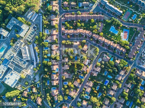 istock An aerial view from the drone of a neighborhood with its swimming pools inside a forest in the outskirts of Madrid city seeing the urban planning of the area with its home and streets aligned 1013345192