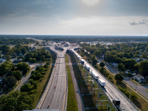 An Aerial View Of A Line Of Semi Trucks Waiting At The Canadian Border To Enter The USA An aerial view of Canada and the United States of semis waiting to cross at The International Border Crossing geographical border stock pictures, royalty-free photos & images